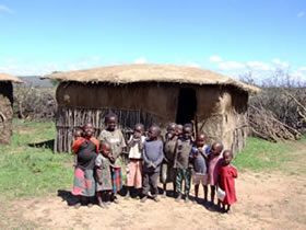 "Maasai children - behind them is a mud hut known as a ""manyatta"""